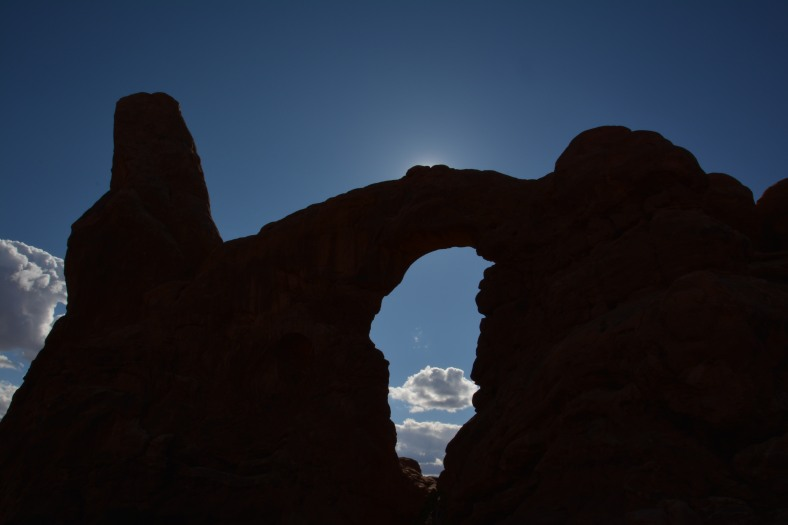 A patch of blue sky, a puffy white cloud, and an arch from ancient times